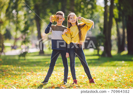 Happy twins teenagers boy and girl posing hugging each other in autumn park holding fallen yellow leaves in hand in sunny weather. Autumn season theme. Brother and sister have fun playing with leaves 70964382