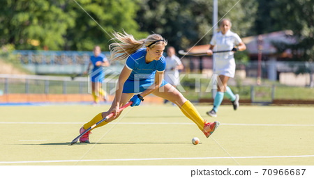 Young field hockey female player hitting the ball 70966687