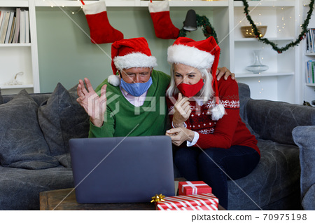Senior couple in santa hat wearing face mask waving while having a video call on laptop at home 70975198