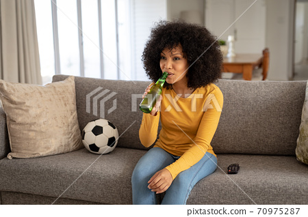 Woman drinking beer while watching sports on TV at home 70975287