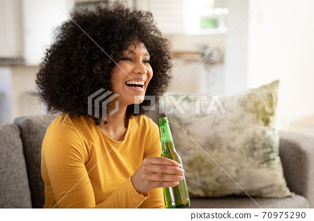 Woman holding beer bottle while watching sports on TV at home 70975290