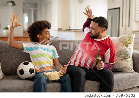 Man and son high fiving each other while watching sports on TV at home 70975302