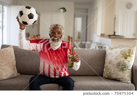 Senior man holding beer bottle and football cheering while watching sports on TV 70975304