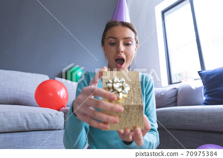 Woman in party hat opening gift box at home 70975384