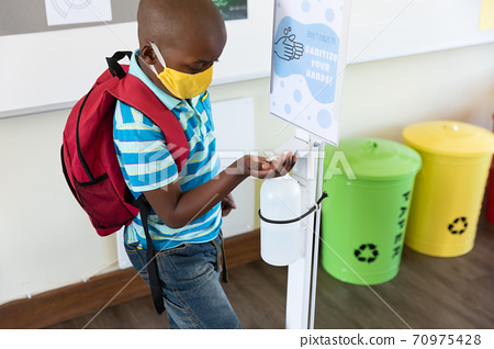 Boy wearing face mask sanitizing his hands at school 70975428