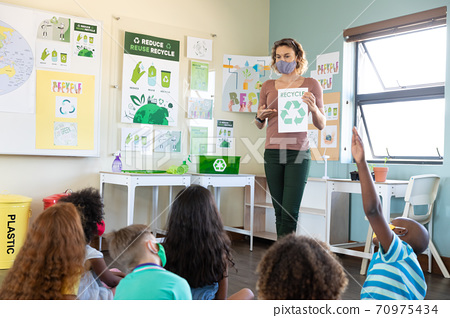 Female teacher wearing face mask showing recycle symbol to students in class 70975434