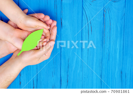 Green paper leaf in hands of adult and child. 70981861