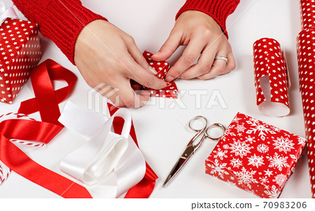 Woman wrapping present in a red paper 70983206