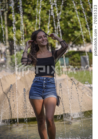 Portrait of young curly brown hair woman smiling outdoors. 70985323