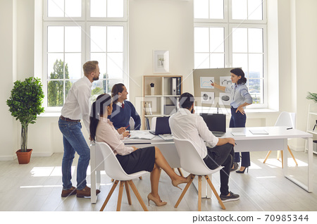 Female chief analyst gives a presentation to a group of economists in a bright office. 70985344