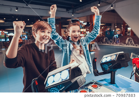 Brother raised hand up and smiles with his sister. 70987883