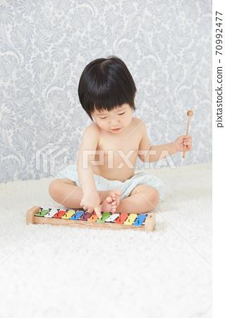 嬰兒與五顏六色的鐵古箏演奏音樂 70992477