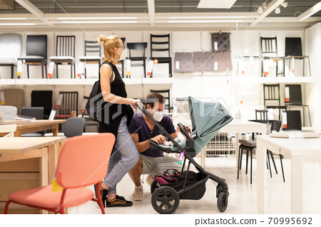 Young couple with newborn in stroller shopping at retail furniture and home accessories store wearing protective medical face mask to prevent spreading of corona virus when shops reopen. 70995692