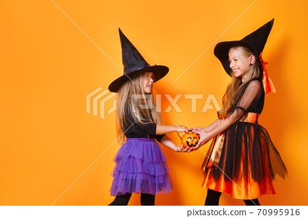 Happy child girls in witch costumes on orange background 70995916