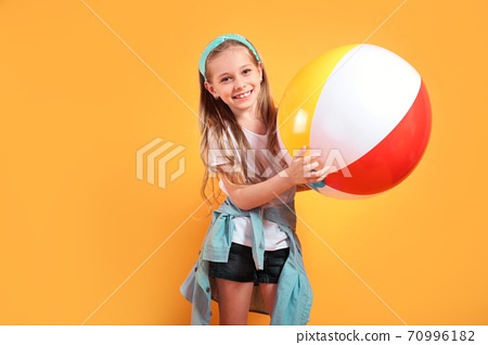 Funny happy child in summer holding beachball on yellow background 70996182
