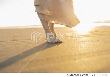 一個女人在沙灘上散步 71002590