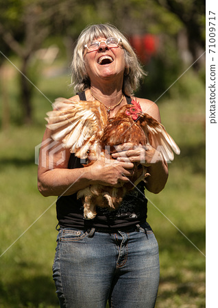 Woman with a red haired laying hen in her arms 71009717