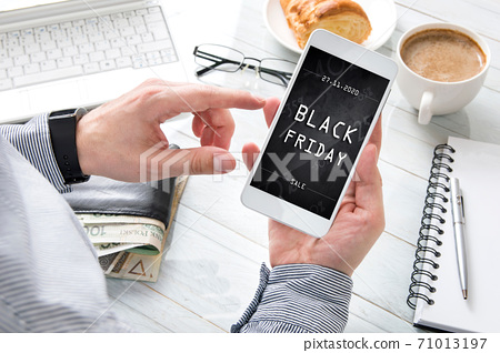 Businessman is holding smartphone with black friday banner on the screen. Conception incoming promotion in e-commerce 71013197