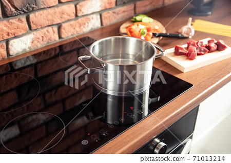 Metal pot stands on a modern induction cooker 71013214