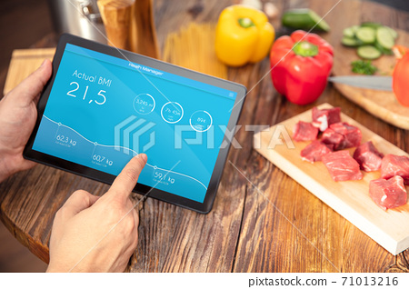 Tablet  with application for BMI calculate over kitchen table with healthy food. Application on the screen created in graphic program. 71013216