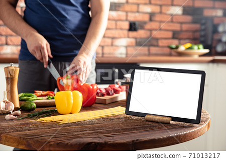 Tablet on the kitchen table and man preparing delicious and healthy food on background. Tablet screen with empty space. 71013217