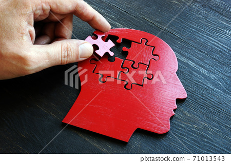 Treating mental illness and memory problems. The hand puts a piece of the puzzle on the shape of the head. 71013543