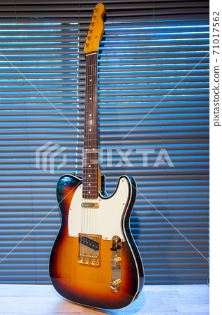 Sunburst electric guitar telecaster shape (gold hardware) on woden table in the room. businoess and music concept. Wallpaper or background 71017562