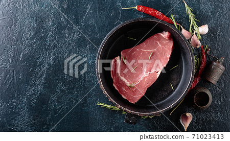 Raw beef steak with spices and herbs. 71023413