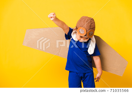 Kid little boy smile wear pilot hat play and goggles with toy cardboard airplane wings 71035566