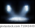 Beautiful ice background. Realistic ice and snow on dark background. Winter background. Spotlight shines on the rink. Bright lighting with spotlights 71043449