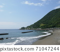 Mountains and coastline on a clear day .... with gentle waves 71047244