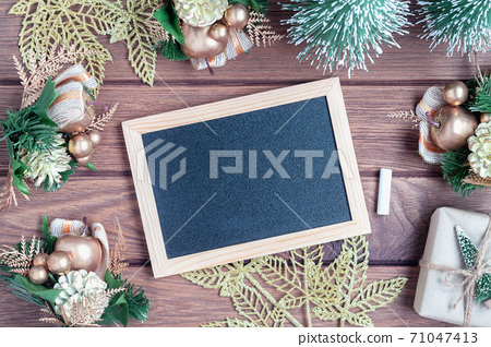 Mockup chalkboard with blank empty screen, new year gift box with Xmas pine tree model, christmas ornaments on wood background, top view, copy space place for your artwork 71047413