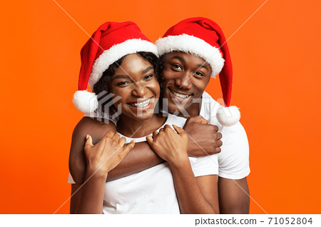 Cheerful black couple in love celebrating Christmas together 71052804