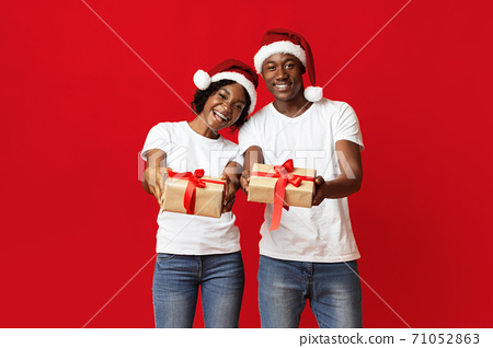 Cheerful black man and woman showing New Year gifts 71052863