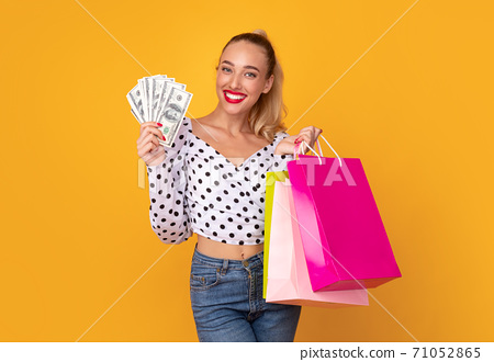 Excited lady holding money and shopping bags 71052865