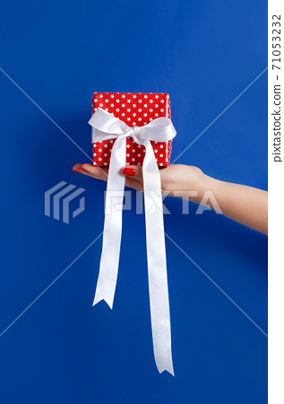 Hand with gift box on blue 71053232