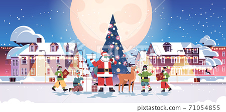 santa claus with mix race elves in masks preparing gifts happy new year merry christmas holidays celebration 71054855