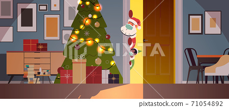 santa with elf in masks peeking out from behind door living room with decorated fir tree new year christmas holidays 71054892