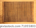 Brown bamboo food mat on wooden table. 71055803