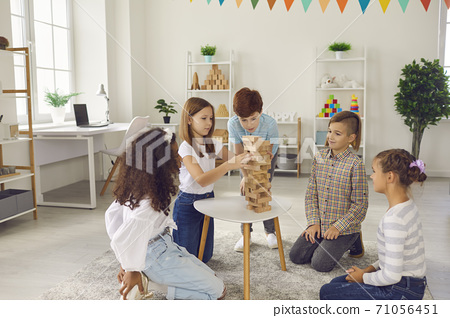 Group of smiling mixed race children sitting on floor and playing with building pyramid 71056451