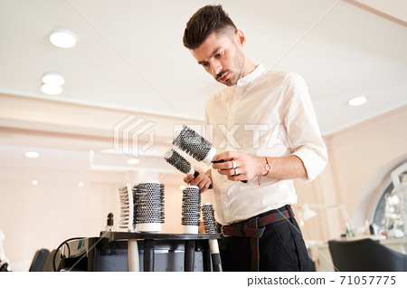 Hairdresser looking at the hair brushes 71057775