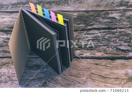 Abstract sketchbook with color note tab. Notebook with colors note tab on wooden table background, Vintage picture tone. 71066213
