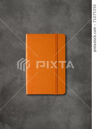 Orange closed notebook on dark concrete background 71075350