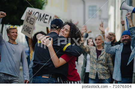 Police stopping group of people activists protesting on streets, women march and demonstration concept. 71076804