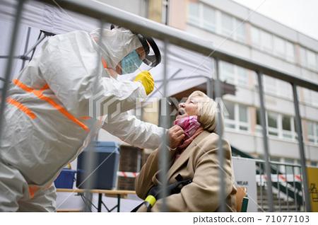Senior woman in covid-19 testing center outdoors on street, coronavirus concept. 71077103