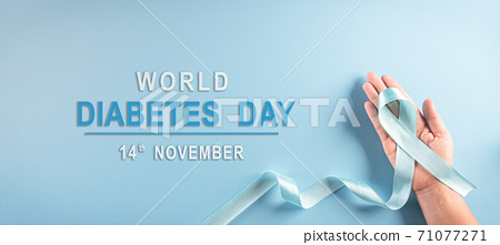 World diabetes day awareness concept. Hand holding blue ribbon, symbolic bow color raising awareness in diabetes day on pastel background,  14 November. 71077271