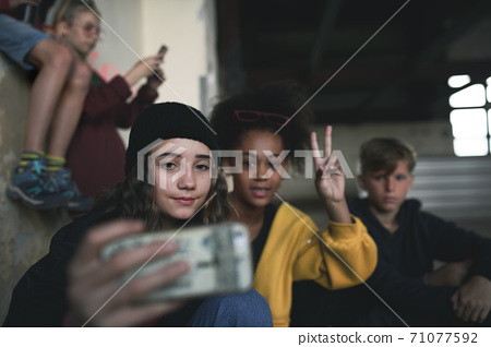 Group of teenagers gang sitting indoors in abandoned building, taking selfie with smartphone. 71077592