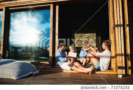 Family with small children sitting on patio of wooden cabin, holiday in nature concept. 71078288