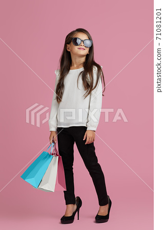 child girl in sunglasses is holding shopping bags 71081201