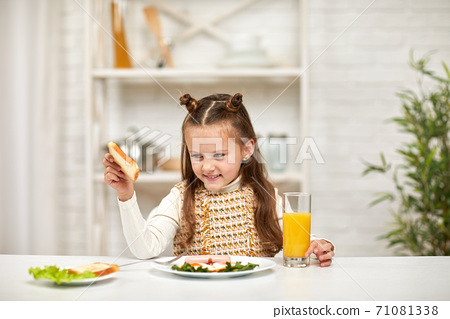 little child girl having breakfast - fried egg and orange juice 71081338